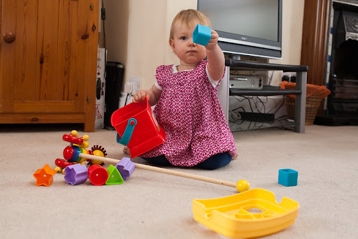 child playing with shape sorter bucket